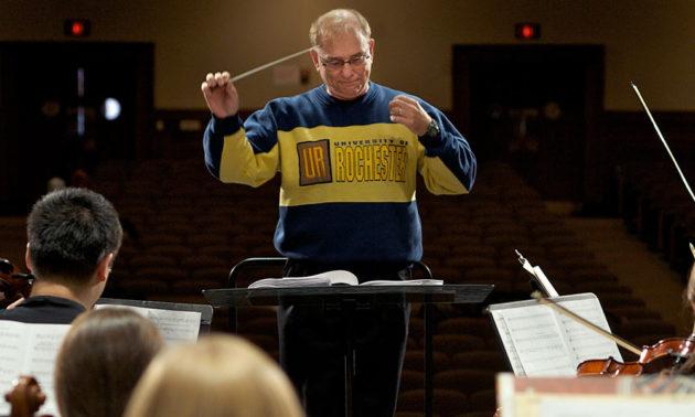man conducting, wearing UR sweater