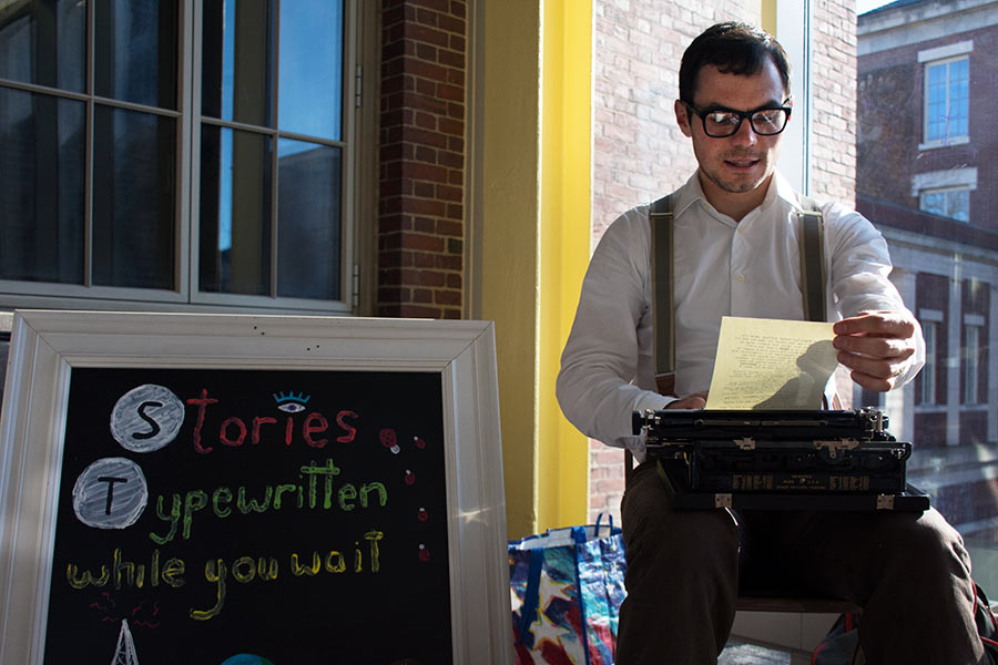"Man in suspenders using an old typewriter and sign reading ""Stories Typewritten while you wait"""