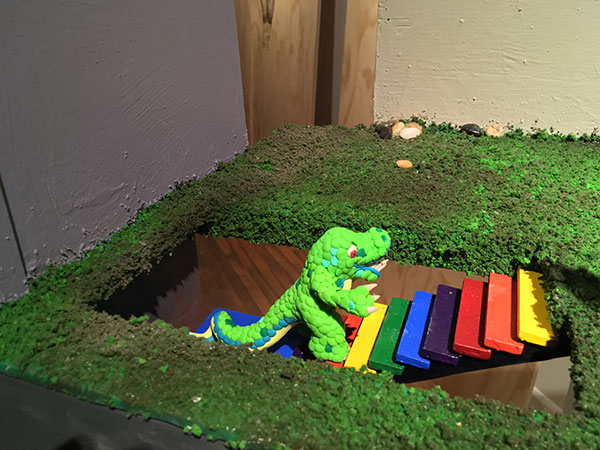 clay model of dinosaur walking up steps