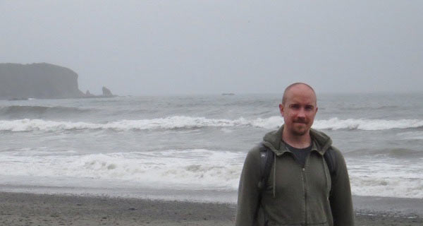 man on a foggy beach studying climate systems