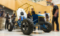 metal framed open air baja car surrounded by students