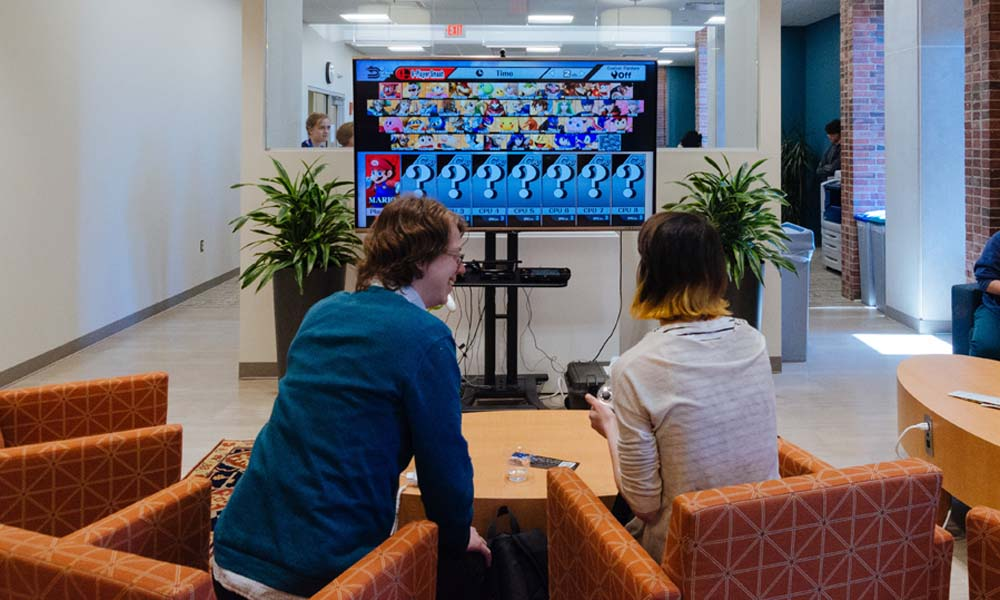 Two Breaking Boundaries participants play a video game in the Humanities Center.