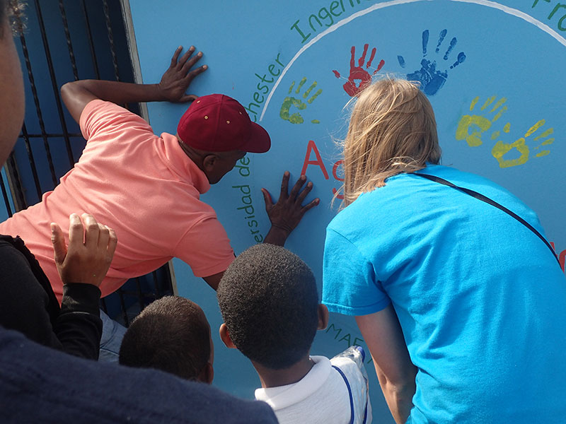 people making painted handprints on a wall