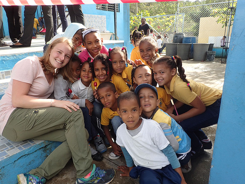 student poses for a photo with a large group of kids