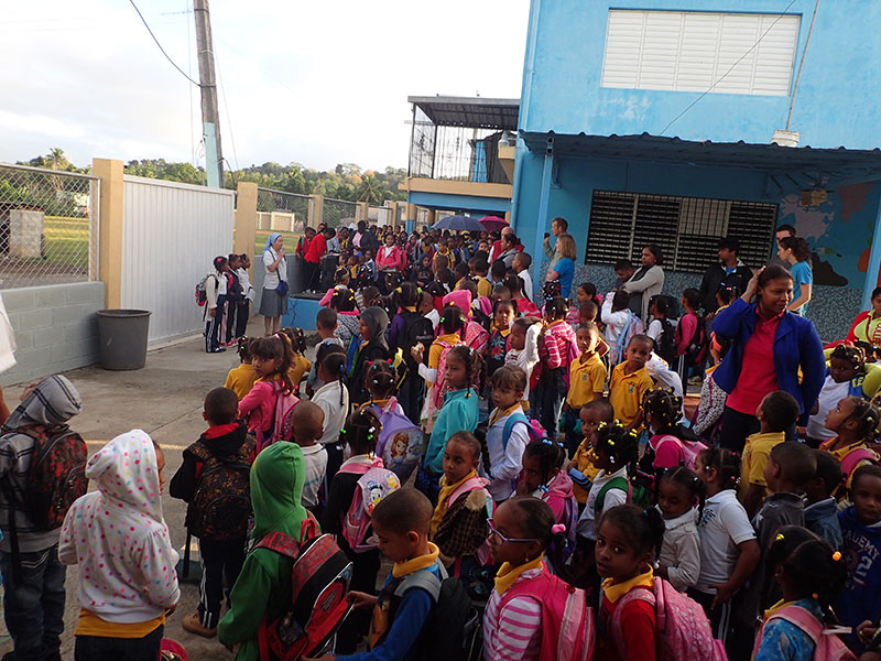 large group of people standing outside a school