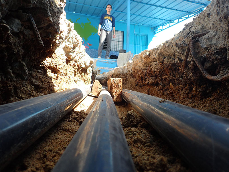 student examines pipes in the ground