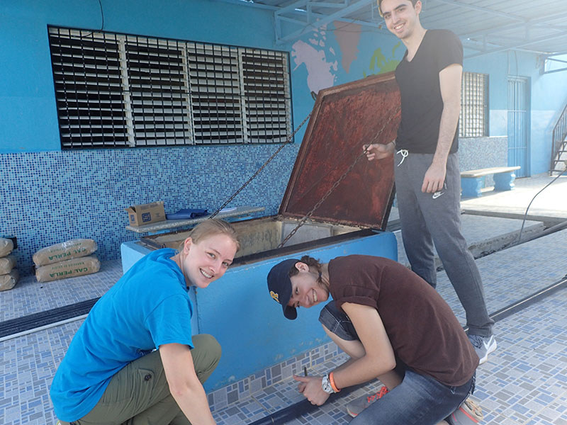 three students looking at water filtration system in brightly painted building