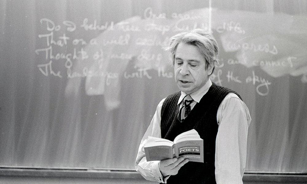 professor reading poetry in front of blackboard