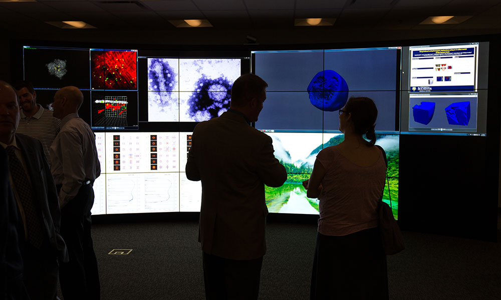 researchers standing in front of large computer displays