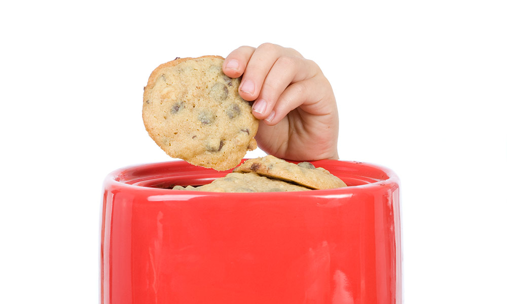 A child's hand reaches and draws a cookie from a jar.