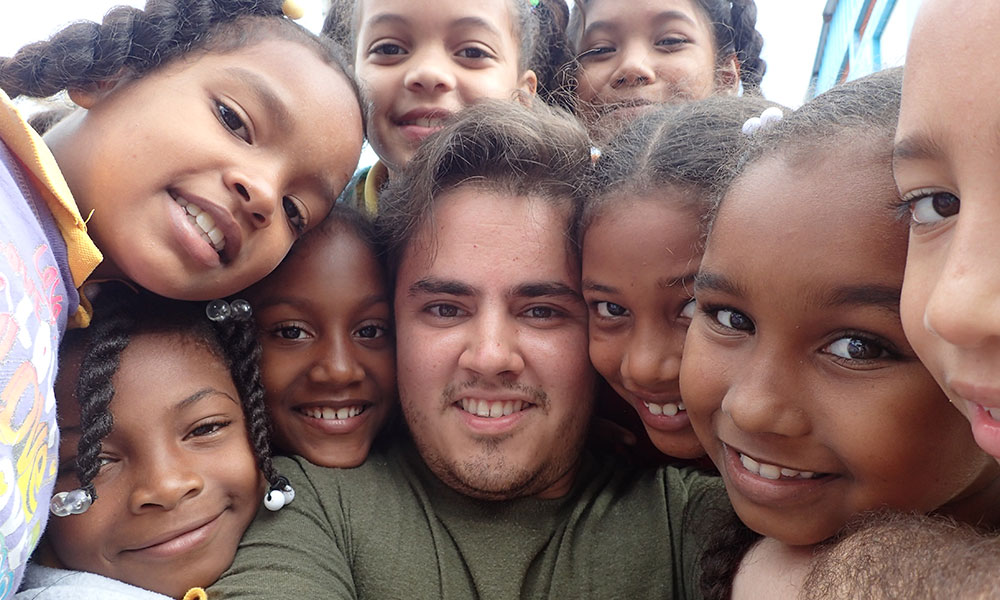student takes a selfie, smiling, surrounded by smiling kids