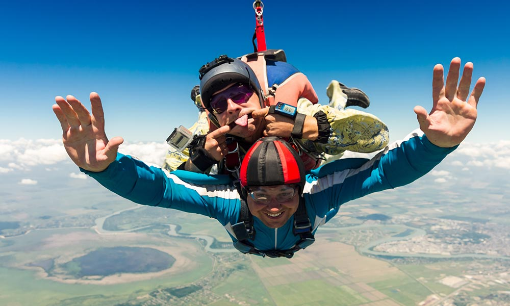two people skydiving while making faces and flashing a thumbs up