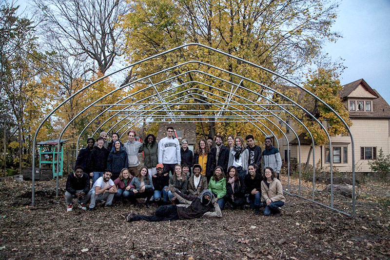 large group of students pose with green house hoop structure