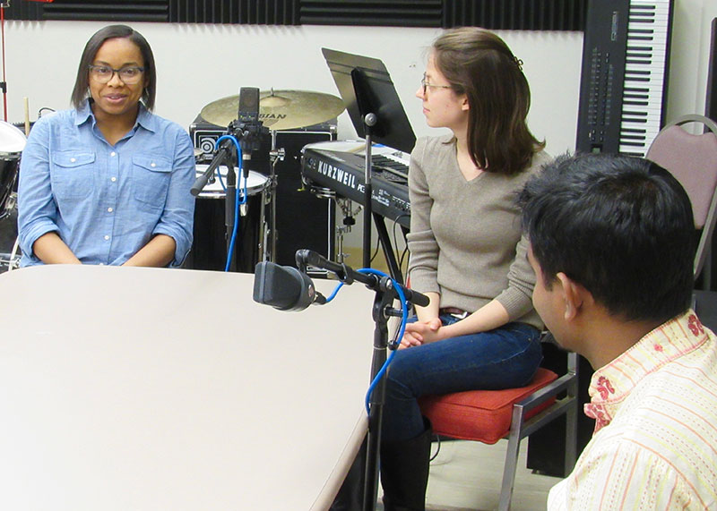 students sitting at a table around a microphone