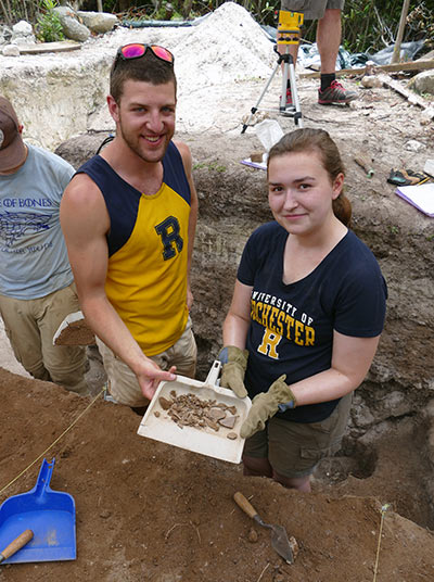 Young man and woman in Rochester shirts hold clay and bone fragments in a dishpan