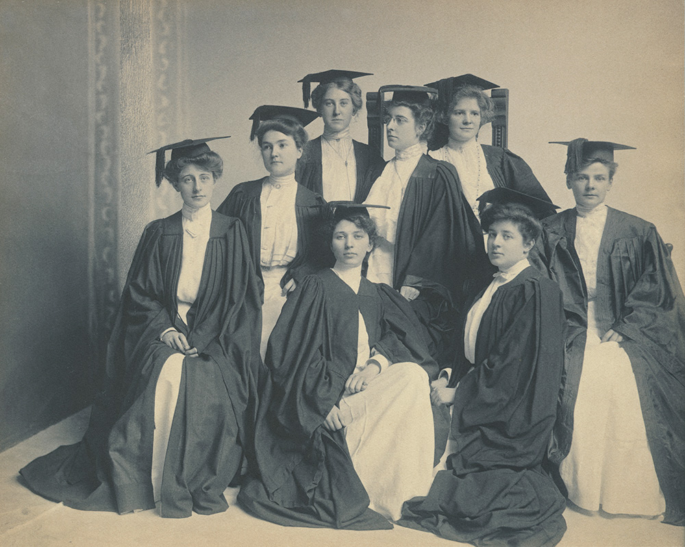 women in Victorian attire and graduation robes.