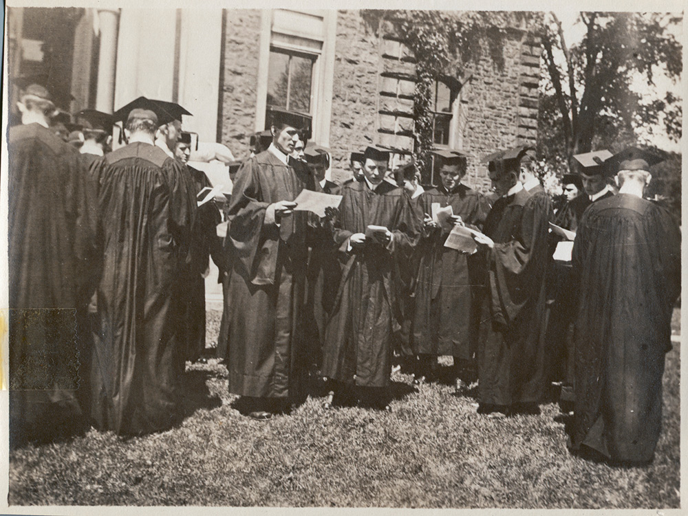 men in graduation robes looking at papers