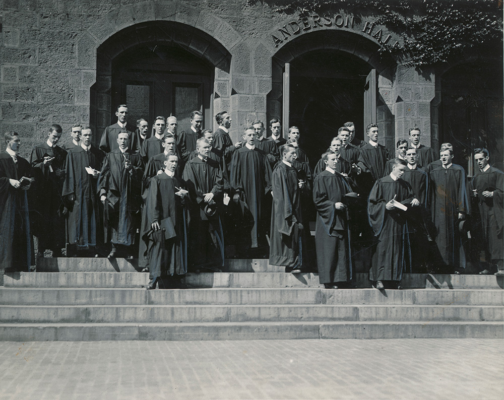 men in graduation robes singing