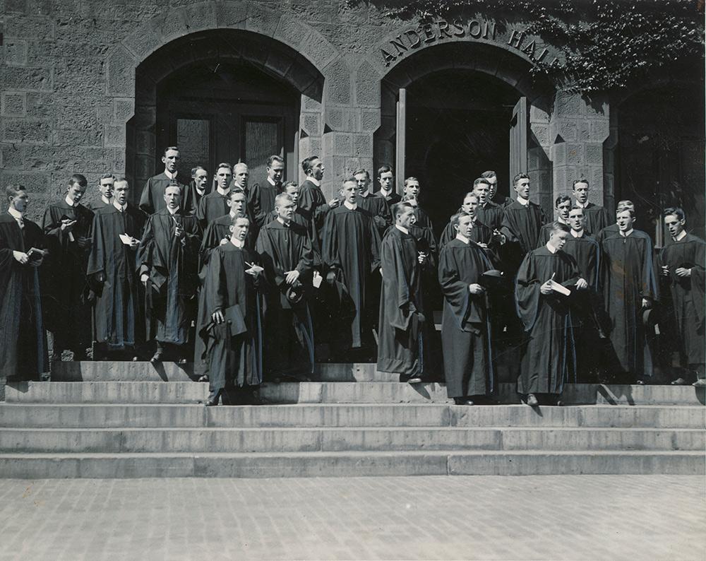 men in graduation robes singing