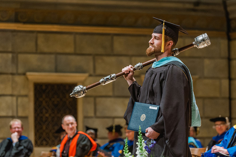 man in graduation robes carries the mace over his shoulder in Kodak Hall