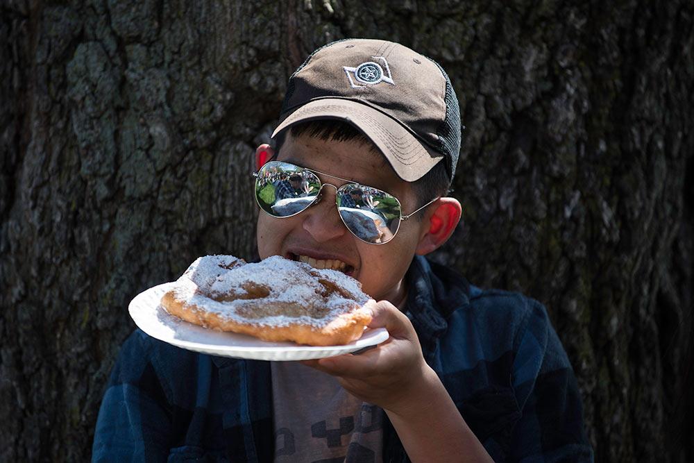 guy in sunglasses eating fried dough
