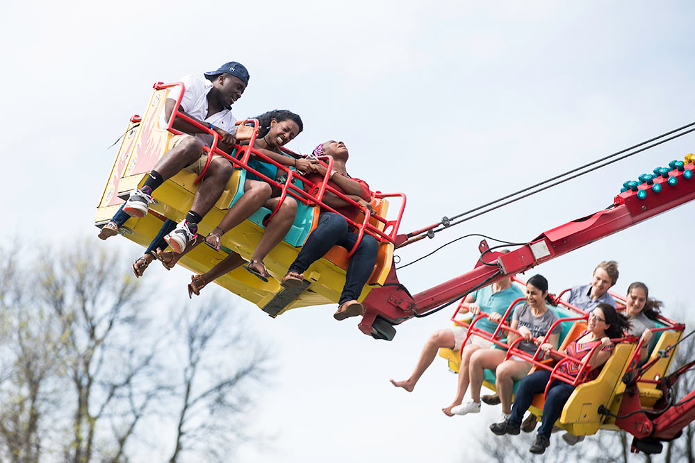 people on a spin ride, with one not looking happy