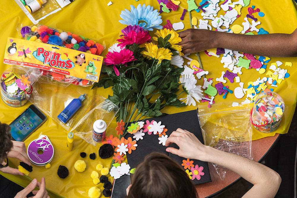 students around a table decorating mortarboards