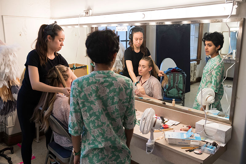 three students backstage, one getting make-up applied in front of a larger mirror