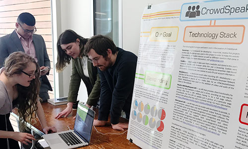 students with laptop and posters