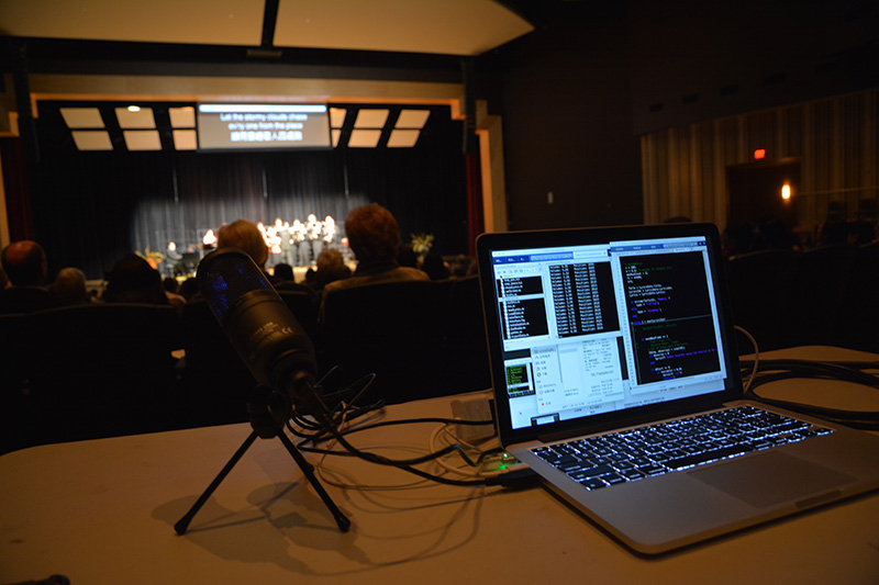 laptop and microphone on a table with performance on stage in the background.