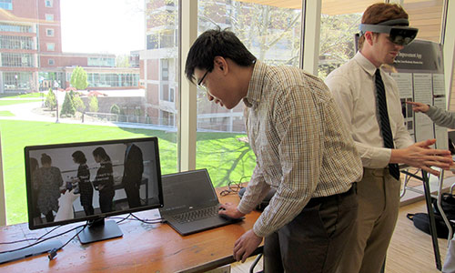 student looking at screen and another wearing virtual reality goggles