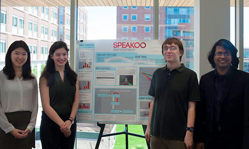 four students by their poster