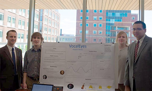 Four students standing by VocalEyes poster
