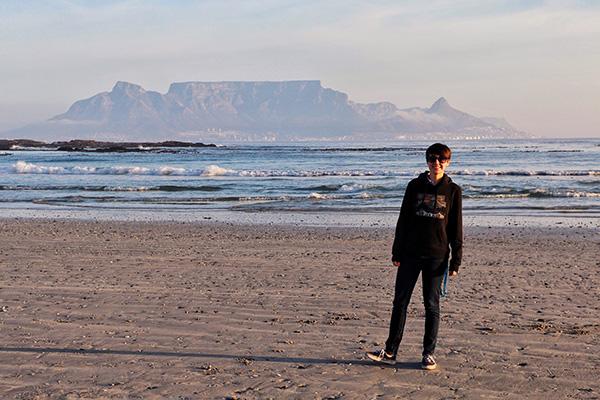 student standing on a beach in South Africa