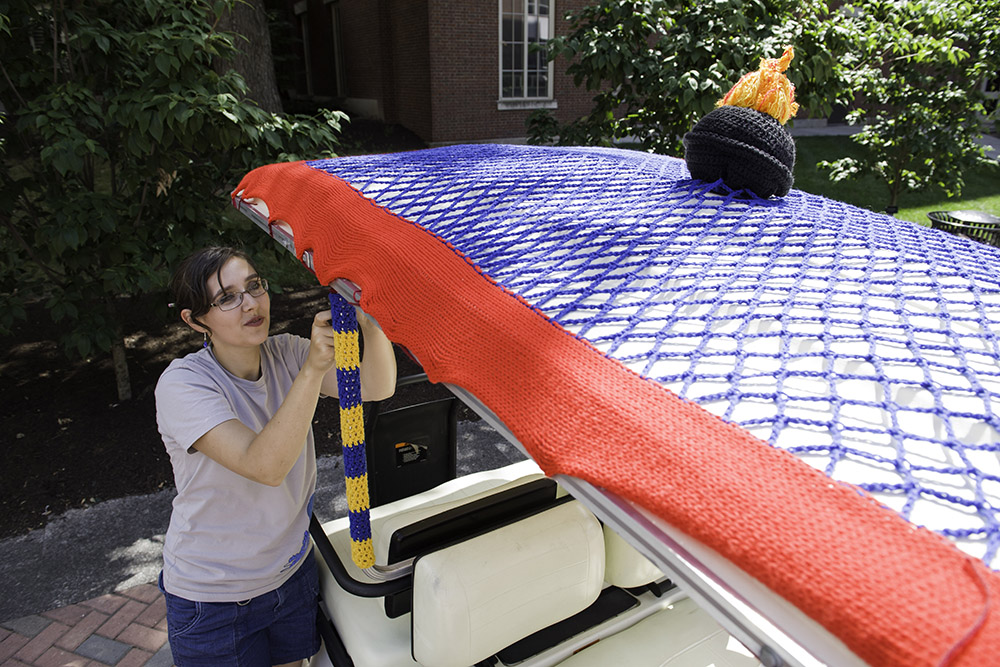 student crochets on golf cart