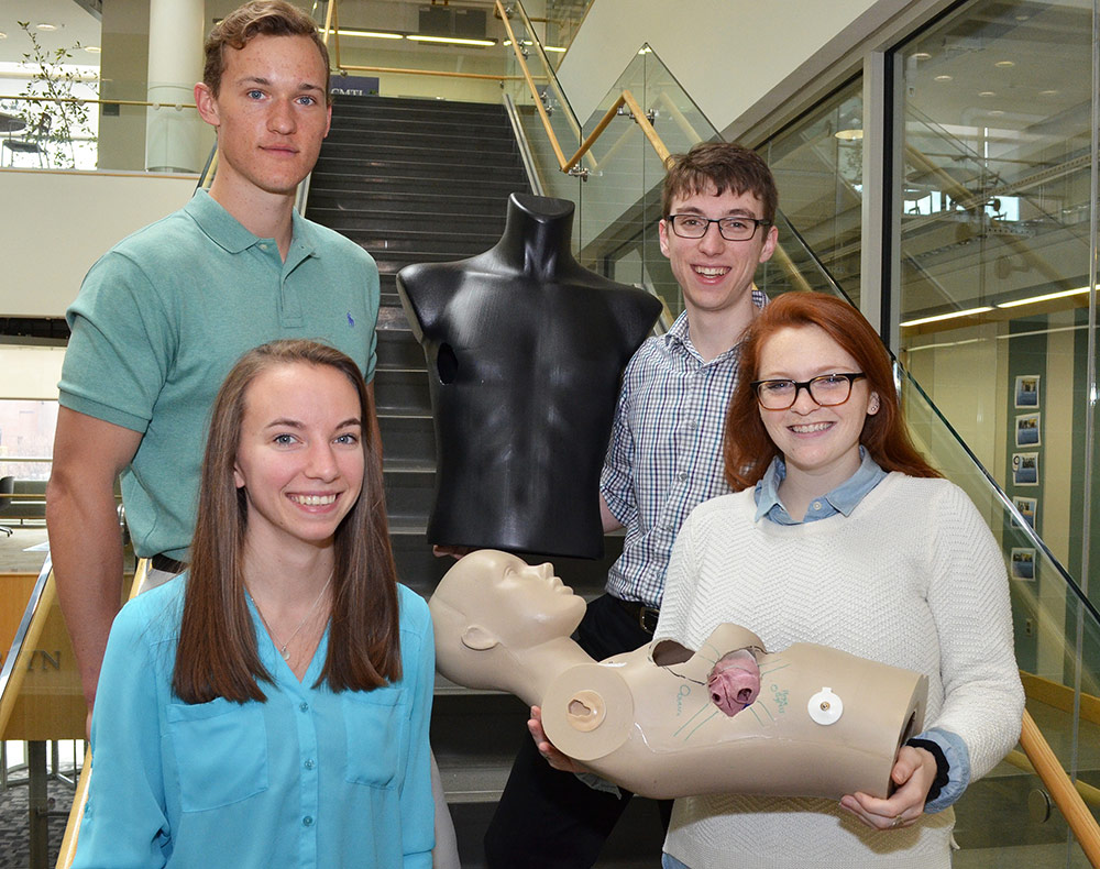 four students, one holding a model of a torso