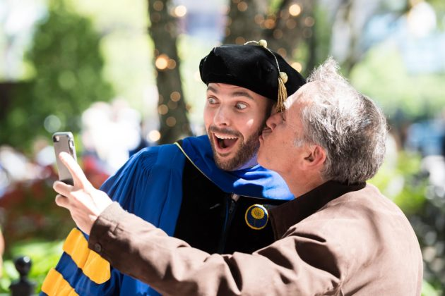 man in graduation garb gets a kiss whil taking a selfie