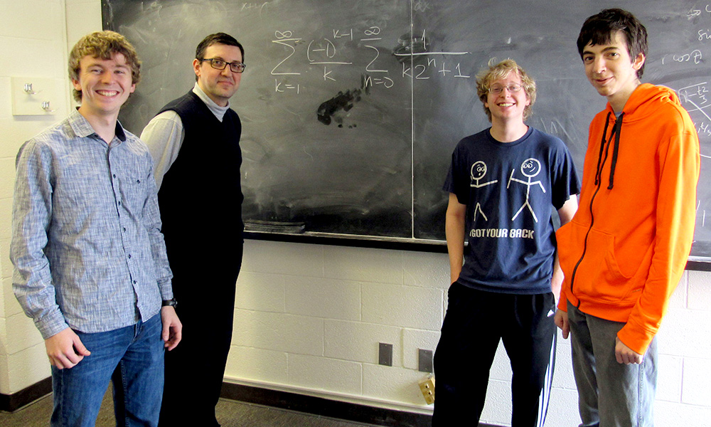 three students and their professor pose in front of a blackboard with complicated math problems on it