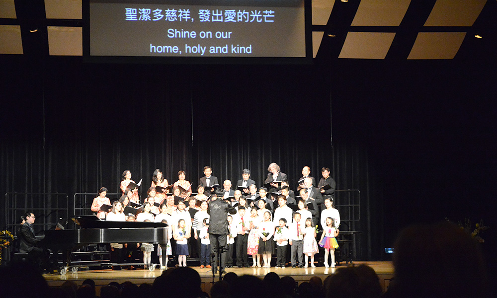 choir performing on stage, with screen above showing lyrics SHINE ON OUR HOME, HOLY AND KIND in English and Chinese
