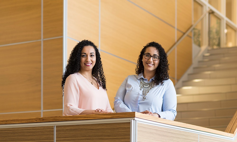two sisters smile while standing in the atrium of LeChase Hall