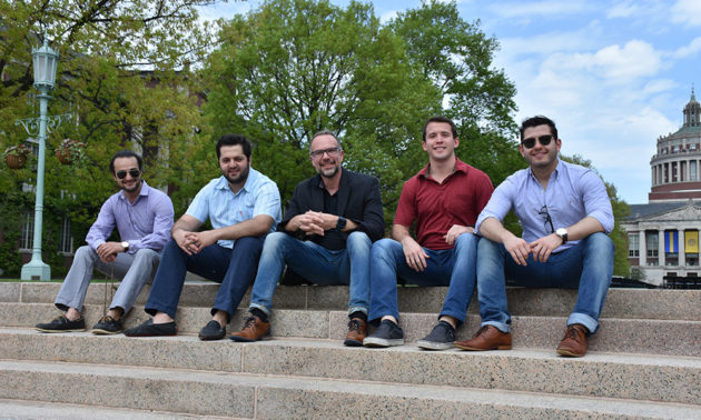 four students and professor pose for a photo on the quad