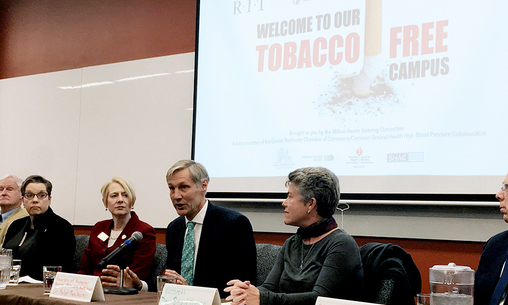 four people speaking at a panel, with screen behind that reads TOBACCO FREE CAMPUS