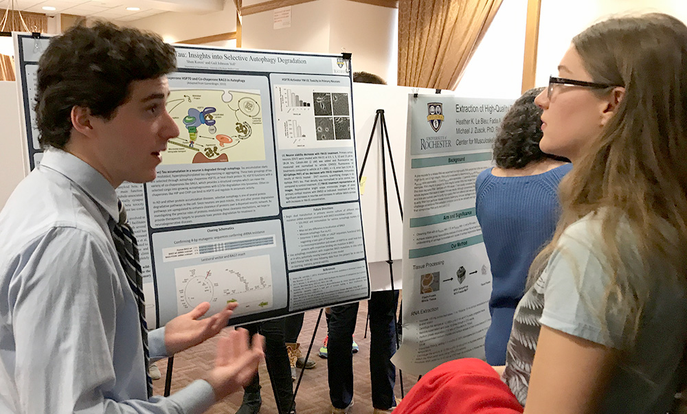 student stands in front of poster, speaking about his research to another student
