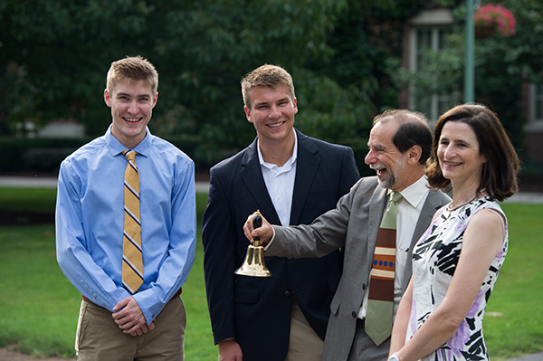 Rich Feldman with two students and Maryann Mavrinac, ringing a bell outside Rush Rhees Library