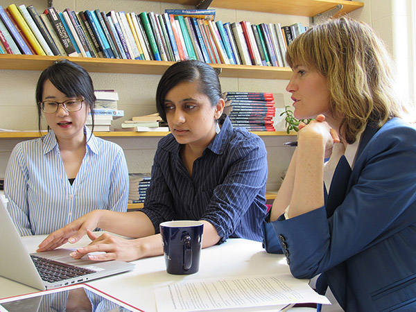 three researchers sitting around a laptop