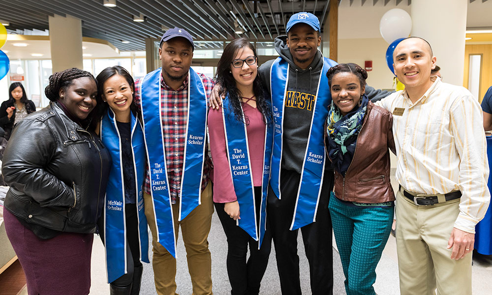 group of students wearing blue stoles and big smiles
