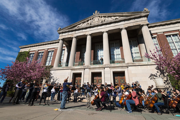 conductor leads an orchestra of musicians in front of Rush Rhees Library