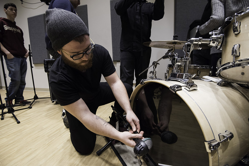 student places mic on drum