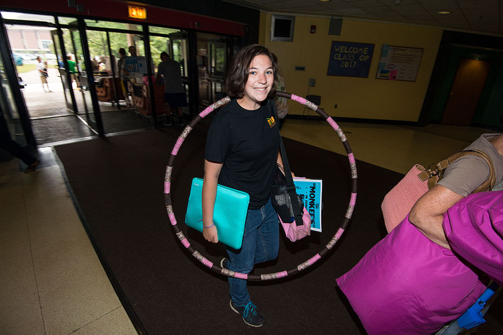 student carrying hula hoop