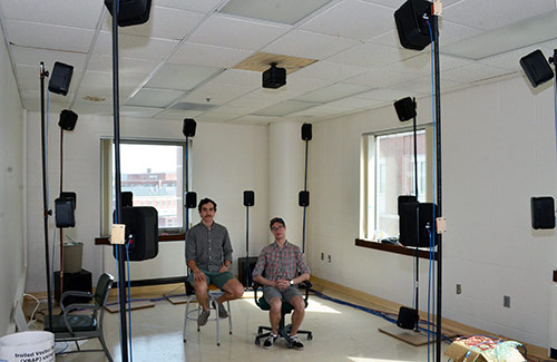 two students in a room surrounded by speakers on poles